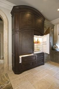 The kitchen features two double integrated Sub-Zero refrigerator-freezers concealed within a large wood armoire as furniture pieces to create a chateau architectural theme.