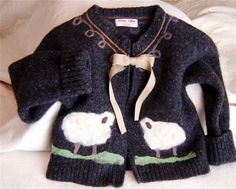 This is a sweet childs cardigan I fashioned from a forgotten cast away adult wool sweater destined for the local landfill. I Fulled it in my washer then turned it from a pullover to a cardigan by...