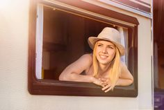 Beautiful woman in a camper van - Beautiful young woman in a camper van on a summer day