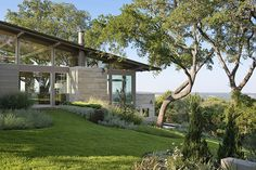 Hill Country house - limestone and glass. All areas of the house were designed to flow directly into the landscape, with ample porches, gardens and outdoor living spaces. Terraced directly into the hill....[onsite building materials.. I say this because just by using local material would save a bundle..let alone the design concept energy efficient home]