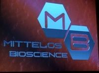 """The Mittelos Bioscience logo. (""""Not in Portland"""") ~ They appear to have considerable wealth and power in the outside world, evidenced by the reach of their front company Mittelos Bioscience. The Others are in possession of the secret knowledge of the bearing by which the Island may be left, and also know how to locate it again to return (though the DHARMA Initiative later discovered reliable ways of getting to and from the Island)."""