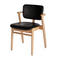 Domus-tuolin selkänoja ja istuin on verhoiltu mustalla nahalla. Runko on lakattua tammea.