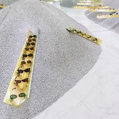 Pop-up shop displays sunglasses on  golden girders embedded in gravel