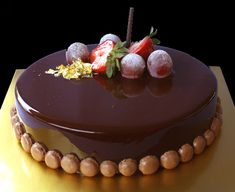 Chocolate Mousse with Glossy Finished (R1) Design R1, Fruit Decoration  Rich chocolate mousse made with premium French chocolate coated with a superb glossy chocolate on the chocolate sponge base. Decorated with macarons or hand crafted chocolates, and a flake of gold.
