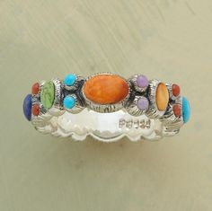 Reminiscent of a Byzantine mosaic, our jewel-encrusted band is encircled with cabochons of lapis, gaspeite, turquoise, coral, spiny oyster shell and sugilite. Sterling silver. Whole sizes 5 to 9.