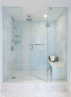 Incredible extra large walk-in shower features a seamless glass door framing a large marble tiled surround which pairs with a linear white and blue glass tiled accent wall over marble tiled floors below a slide bar shower head and square shaped rainfall shower head across from a waterfall edge shower bench which completes the space.