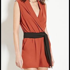 Rust/Black Contemporary Romper Brand new woven romper with a sleeveless cut, a shawl collar, a surplice front, a self-tie belt, an elasticized waist, and slanted front pockets. 100% polyester. Forever 21 Other