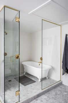 clawfoot tub in glass enclosed shower