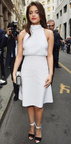 Odeya Rush wearing a pale sleeveless high-neck top over a knee-grazing skirt, with a chain-strap purse and two-tone sandals.