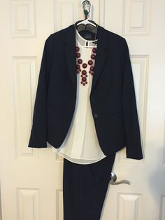 Navy pants, navy jacket, cream blouse, red necklace