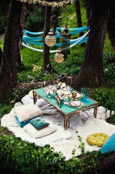Tapete peludo de color blanco sobre el pasto. Almohadones originales en tonos contrastantes y neutros. Mesa ratona en turquesa y dorado, a tono con los individuales y jarra de vidrio. Copas de vidrio grueso y centros de mesa con flores. Guirnaldas de tela y papel colgadas entre los árboles y faroles decorando. El bosque de Mar de las Pampas es el entorno ideal para hacer una romántica propuesta.