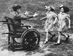 Two little girls rush into the outstretched arms of their wheel chair bound father. He is a casualty from the British Expeditionary Force in France. June 9, 1940 (Photo by Reg Speller/Fox Photos/Getty Images)