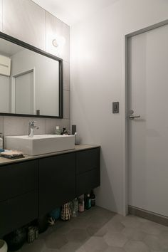 大きめのタイルを張った壁と、黒の縁の鏡がシックな洗面所。