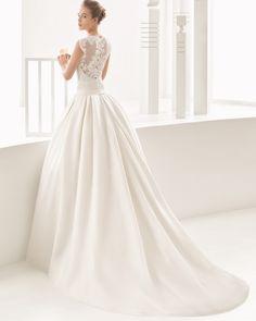 Abito classico haute couture con corpetto di guipure, base con scollo a cuore e gonna di garza di seta, taglio alto sui fianchi con pieghe e tasche. Colore avorio.