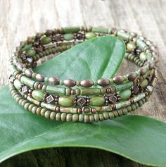 Stacked beaded bracelets - Earthy green turquoise stones combine with aged picasso Czech glass and oxidized copper to wrap around your wrist 5 times in one continuous coil. Strung on sturdy memory wire, it creates the illusion of five separate bracelets. No clasp, no fuss. A perfect
