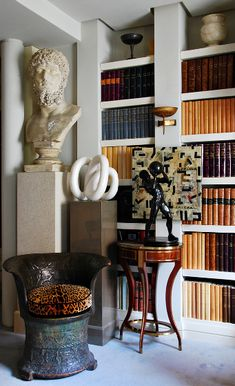 Overscale sculpture on pedestals combining design eras hug sculptural bookcases filled with color coded neutral antique books. Striking design in living room