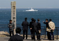 Image: A Japanese Coast Guard vessel PS08 Kariba sails off Cape Nosappu in Nemuro on Japan's Hokkaido island, with part of the islands known as the Northern Territories in Japan and the Southern Kurils in Russia visible the background