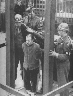 Five German civilians were tried and found guilty of the murder of six American fliers who parachuted down upon Germany from a disabled plane in 1944. Johann Seipel, the first to be hanged, has only a few seconds to live. The noose has been fastened about his neck and the hood is being placed over his head preparatory to springing the trap at the Bruchsal Prison, Germany. November 10, 1945.