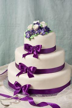 Wedding cake with purple ribbon.