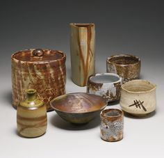 A GROUP OF JAPANESE TEA CEREMONY WARES 20TH CENTURY comprising a Shino Mizusashi water container by Junzo; a Bizen-style triangular vase; a Bizen rust-splashed Tokkuri (sake bottle); a Shino cylinder-form teacup; and four other teabowls including a Totoya bowl by Takeuchi, an Oribe-style white-glazed bowl, another gray and rust-colored Shino bowl by Koyama II, and another Bizen Imbe bowl, each with a Japanese wood box. Height of tallest 8 1/2 in