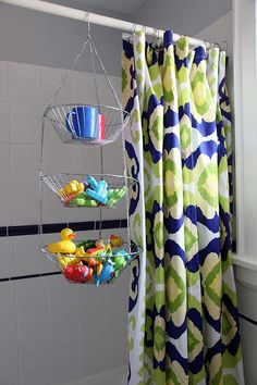 Metal hanging fruit basket over the shower curtain rod to hold all the toys