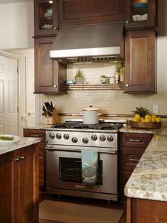 Lovely Kitchen, Vivacious Backsplash Behind Large Stainless Steel And Metal Stove All Mounted Range Hood Kitchen Island With Marble Countertops Wooden Cutlery Set Wooden Fruit Serving Bowl Hardwood Laminate Floor Small Kithcen Remodel: Under Cabinet Range Hoods