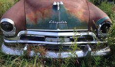 Old car in the field by a winery
