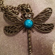 "Dragonfly necklace This beautiful Dragonfly hangs on a 28"" chain. This is costume jewellery, stones and metal are not real. Turquoise colored stone sits between the wings and 2 clear stones as its eyes. The Dragonfly itself is about an inch and a quarter long and 2"" across. The chain and the rest of the Dragonfly are a dull brassy color. Jewelry Necklaces"