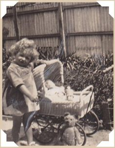 This pretty little girl has it all: a buggy, baby dolls, a teddy bear, and a sunny day. Vintage snapshot photo.