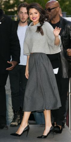Selena Gomez in a cropped sweater and a gray midi skirt with black pumps.