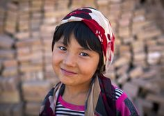 "Uyghur girl in Kashgar, Xinjiang China Smiling in front of the bricks that will be used to build the new ""old"" town... © Eric Lafforgue"