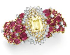 A DIAMOND, RUBELLITE TOURMALINE AND YELLOW SAPPHIRE BRACELET, BY DAVID WEBB Set with a rectangular-cut yellow sapphire, within a circular-cut diamond foliate surround, to the variously-shaped rubellite tourmaline cluster band with circular-cut diamond detail, mounted in gold and platinum, circa 1966