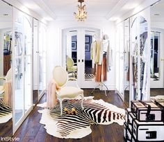 Mirrored walk in closet with white decor and a zebra print rug against a wooden floor