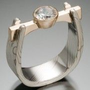 Flat Beam Setting, with .75 Carat Diamond; unusual and interesting setting. Also the contrast between the wide band and the narrow beam manages to retain the delicacy for, say, a wedding ring, while also being chunky and contemporary.
