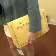 """Studded Envelope Style Clutch NWT. Yellow with silvertone studs on one side. Silvertone hardware. Accordion bottom with full length zipper. Extra strap, detachable, included. 2 interior, open pockets. Dimensions: 14.5"""" wide x 9.25"""" tall x 2.5"""" wide at bottom. Adjustable strap is 50"""" including hardware. Faux leather. White also available in a separate listing. Mad About Style Bags Clutches & Wristlets"""