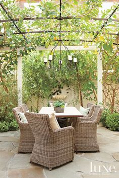 Wood created a secret-garden feel for an outdoor dining area with plenty of greenery and a wall-mounted clamshell fountain. The chairs are by Kingsley- Bate, and the custom light fixture is from Wood's shop, Molly Wood Garden Design.
