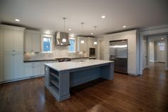 This L-shaped kitchen with a large island has white wall cabinets and grey island cabinets with white marble counters and stainless steel appliances. Pendant lights over the island complete the design. One Wall Kitchen, Best Kitchen Cabinets, New Kitchen, Kitchen Appliances, Wall Cabinets, Kitchen Grey, Grand Kitchen, Kitchen Tips, Kitchen Layouts With Island