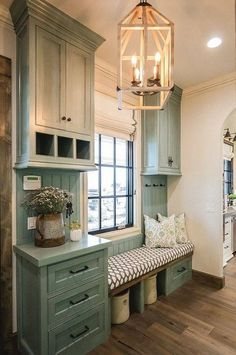 Country chic green cabinet mud room with bench.