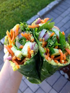 Collard wraps with edamame hummus, lime juice, red onion, carrot, cucumber, arugula, and black pepper.