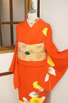 ほのかにスモークがかった深みのある綺麗なスカーレット色の地に、大輪の向日葵模様が染め出された付下げ着物です。