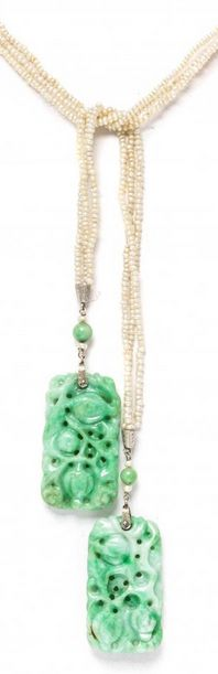A Platinum, White Gold, Jade and Seed Pearl Bead Lariat Necklace, Circa 1910, consisting of three seed pearl (origin not tested) strands strung with engraved platinum gathers suspending two spherical jade beads and four pearls extending to the engraved white gold bails and carved mottled green jade plaques depicting foliate scenes and measuring approximately 33.00 x 19.00 mm each.