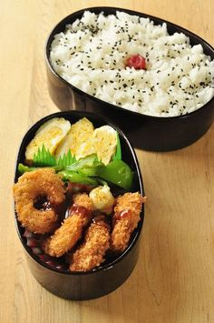 Fried squid rings bento box, featuring sides of tamagoyaki, and sesame rice with umeboshi