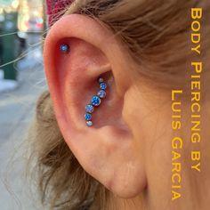 Conch piercing by Luis Garcia of NoKaOi Tiki Tattoo. Jewelry by Anatometal.