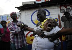 Armante Cherisma cries in front of the body of her daughter, Fabienne, 15 years old, killed by a policeman while looting wall hangings in the Marthely Seiee street January 19, 2010 in Port-au-Prince, Haiti.