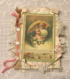 altered textile art, mixed media Christmas card, vintage image, vintage millinery, french fibers, ribbon, circa 1910 music and journal paper, aged cheesecloth, lace snippets….needletraditions design...