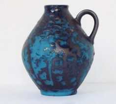 This small, Fat Lava vase was produced by Carstens Tönnieshof of West Germany. It features a dark blue base glaze with a thick, black Fat Lava glaze.
