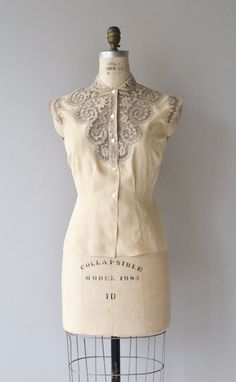 Vintage 1950s cream silk & cotton blend sleeveless blouse with cutout lace and gray trimmed upper bodice, tiny collar, and darted waist for a fitted