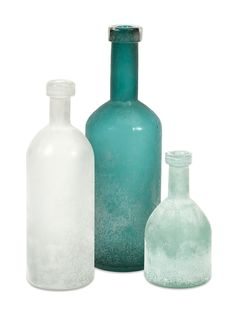 Like weathered sea glass, this trio of glass bottles in soothing shades of aqua, soft turquoise and white appear frosted by tumbled sea water and sand. Sea-Washed Aqua and White Bottles - Set of 3