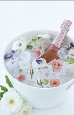 rose champagne in ice bucket with frozen flower ice cubes.