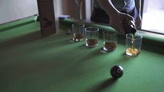 cinemagraph animated gif of pouring whisky into glasses on pool table at wedding